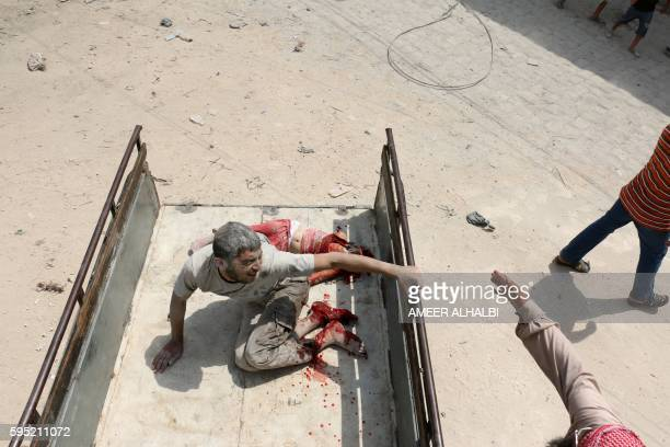 Graphic content / A wounded Syrian man sits in the back of a truck next to a dead girl following a barrel bomb attack on the Bab alNairab...