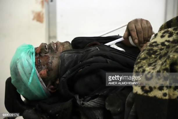 Graphic content / A wounded Syrian man waits for treatment at a makeshift clinic during Syrian government air strikes on Zamalka in the rebel enclave...