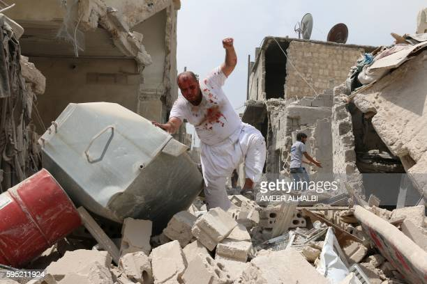 Graphic content / A wounded Syrian man walks in the rubble of buildings following a barrel bomb attack on the Bab alNairab neighbourhood of the...