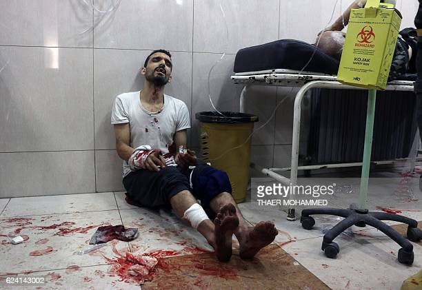 Graphic content / A wounded Syrian sits on the floor in a crowded makeshift hospital in eastern Aleppo as regime aircraft and artillery pounded...
