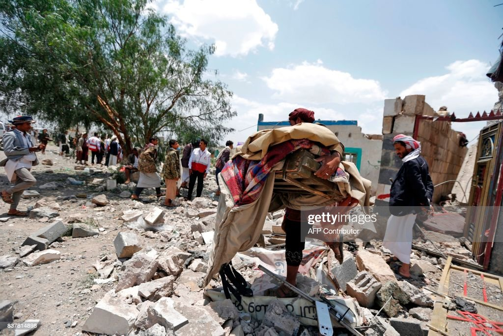 Graphic content / A Yemeni man carries his belongings at the site of an air raid in the Arhab area, around 20 kilometres (13 miles) north of Sanaa, on August 23, 2017, where a Saudi-lead coalition has been bombing Iran-backed Huthi rebels. The Huthis, who control Sanaa along with forces loyal to former president Ali Abdullah Saleh, blamed the pro-government Arab military coalition for the attack on Arhab district. / AFP PHOTO / Mohammed HUWAIS