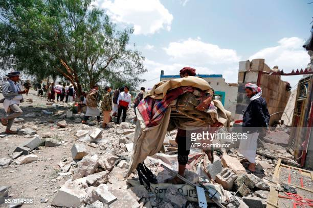 Graphic content / A Yemeni man carries his belongings at the site of an air raid in the Arhab area around 20 kilometres north of Sanaa on August 23...