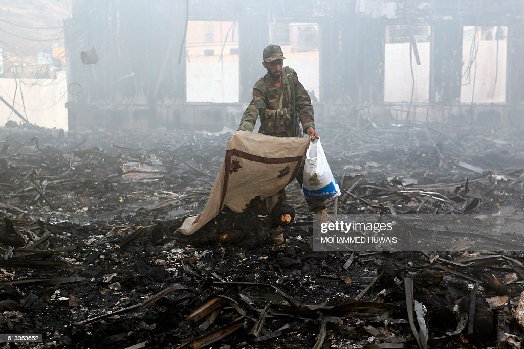 Graphic content / A Yemeni man covers a charred body amid the rubble of a destroyed funeral hall building following reported airstrikes by Saudi-led coalition air-planes on the capital Sanaa on October 8, 2016. Rebels in control of Yemen's capital accused the Saudi-led coalition fighting them of killing or wounding dozens of people in air strikes on Sanaa. The insurgent-controlled news site sabanews.net said that coalition planes hit a building in the capital where people had gathered to mourn the death of an official, resulting in 'dozens of dead or wounded'. / AFP / MOHAMMED