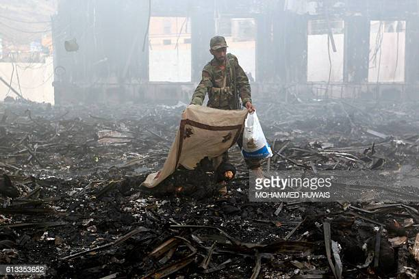Graphic content / A Yemeni man covers a charred body amid the rubble of a destroyed funeral hall building following reported airstrikes by Saudiled...