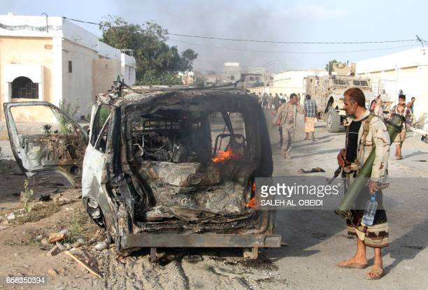 Graphic content / A Yemeni man looks at a burning vehicle following a reported suicide car bombing in Huta the capital of the southern province of...