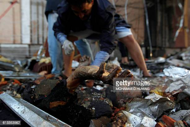 Graphic content / A Yemeni rescue worker kneels towards a charred body amid the rubble of a destroyed funeral hall building following reported...