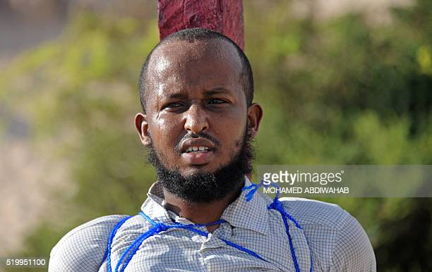 Graphic content / Abdirisak Mohamed Barow one of the two somalian men convicted of murdering a Somali journalist are tied to wooden posts before...