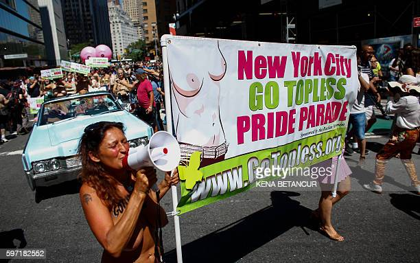Graphic content / Activists hold posters as they take part in the GoTopless Pride Parade on August 28 2016 in New York Women around the US are going...