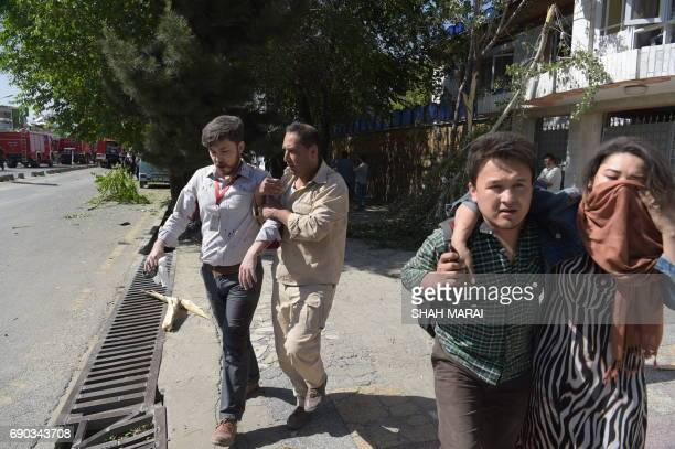Graphic content / Afghan men provide assistance to the wounded at the site of a car bomb attack in Kabul on May 31 2017 A massive blast rocked...
