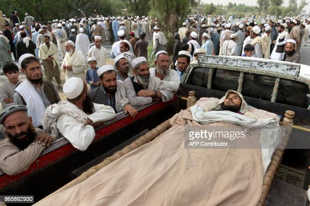 Graphic content / Afghan men stand around the body of a man killed during an overnight raid by the Afghan forces' on October 23 at Mohmand Dara...