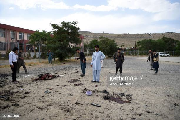 Graphic content / Afghan men stand by human remains at the site of a series of explosions that targeted a funeral of a politician's son who was...