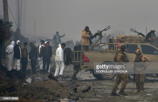 Graphic content / Afghan security forces and investigators gather at the site of a suicide bomb attack outside a British security firm's compound in...