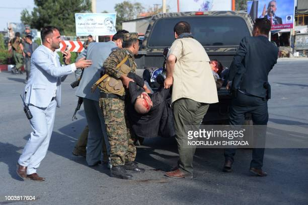 Graphic content / Afghan security forces placed victims on the back of a pickup truck following a suicide attack in Kabul on July 22 2018 A suicide...