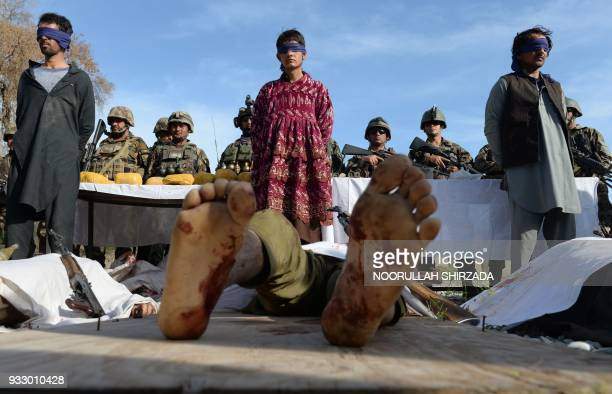 Graphic content / Afghan security personnel stand guard near three Taliban fighters and the bodies of other Taliban fighters lying on the ground as...