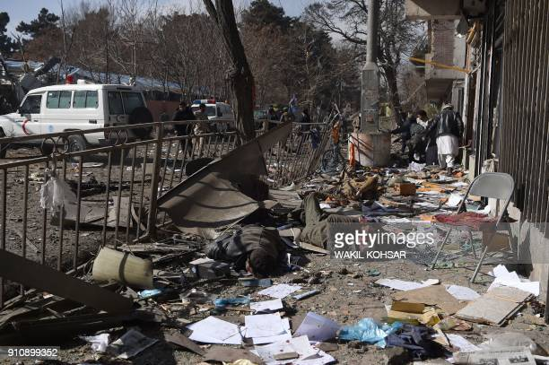 Graphic content / Afghan volunteers carry bodies at the scene of a car bomb exploded in front of the old Ministry of Interior building in Kabul on...
