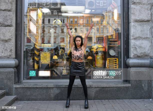 Graphic content / An activist of women's rights movement of Femen bearing the words 'Black Friday' on her chest protests in front of a store in Kiev...