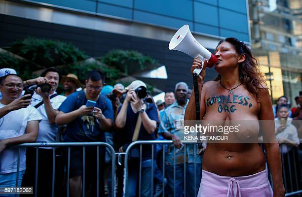 Graphic content / An Activist speaks to the crowd as she takes part in the GoTopless Pride Parade on August 28 2016 in New York Women around the US...