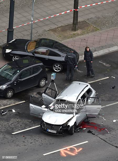 Graphic content / An aerial view shows police officers standing near the wreckage of a car after a blast caused by an explosive device killed its...