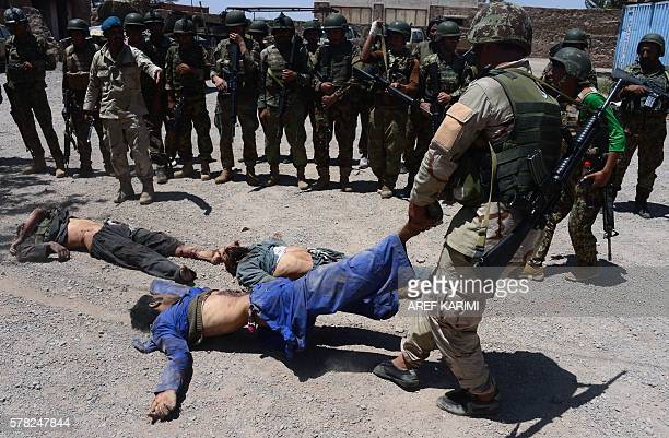 Graphic content / An Afghan commando pulls one of the bodies of six Taliban militants who were killed by Afghan cammandos in Adraskan district some...