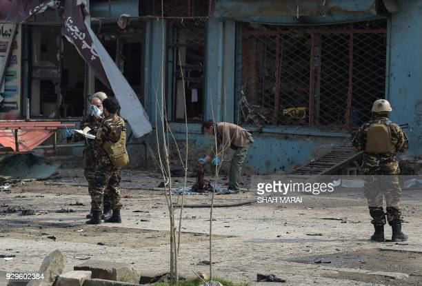 Graphic content / An Afghan investigator inspect the remains of a body at the site where a suicide attacker blew himself up in a Shiite area of Kabul...