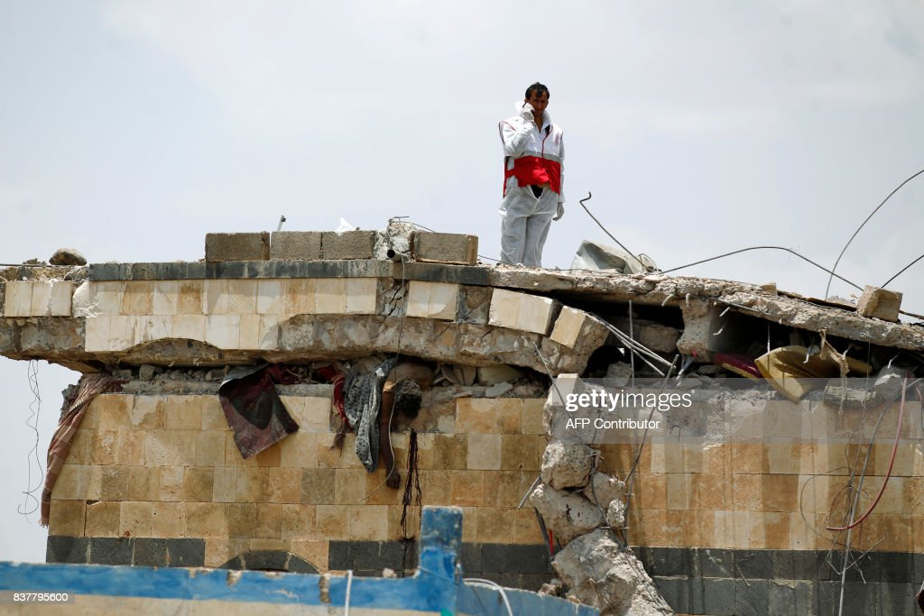 Graphic content / An aid worker stands above the body of a man stuck under the collapsed roof of a building hit in an air raid in the Arhab area, around 20 kilometres (13 miles) north of Sanaa, on August 23, 2017, where a Saudi-lead coalition has been bombing Iran-backed Huthi rebels. The Huthis, who control Sanaa along with forces loyal to former president Ali Abdullah Saleh, blamed the pro-government Arab military coalition for the attack on Arhab district. /