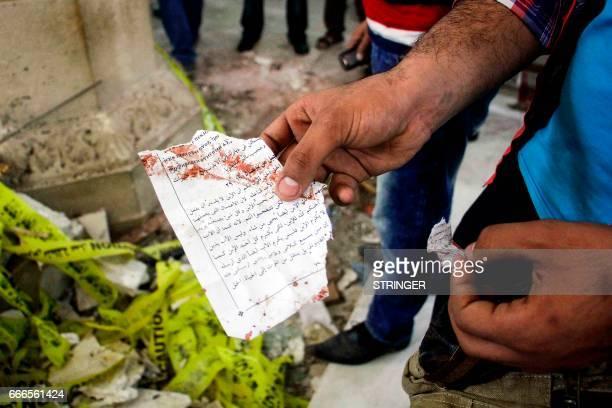 Graphic content / An Egyptian holds out torn a page from a prayer book showing a section of the Gospel of John in Arabic inside the Mar Girgis Coptic...