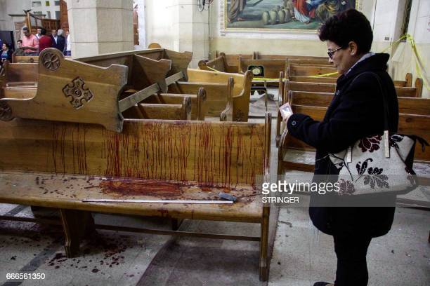 Graphic content / An Egyptian woman uses her cell phone to take pictures of the destruction debris and bloodstains inside the Mar Girgis Coptic...