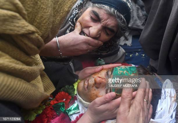 Graphic content / An elderly woman cries over the body of slain teenaged militant Mudasir Ahmad Parrey during a funeral procession in Hajin, north of...