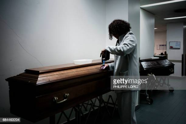 Graphic content / An employee prepares a coffin at the morgue of the Hospital Bichat Claude Bernard in Paris on May 11 2017 / AFP PHOTO / PHILIPPE...