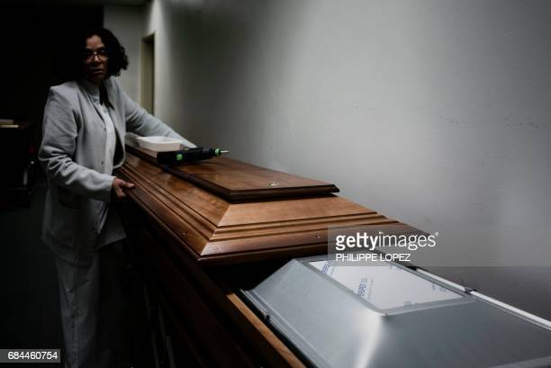 Graphic content / An employee prepares a coffin specially made for long distance and international travelling at the morgue of the Hospital Bichat...