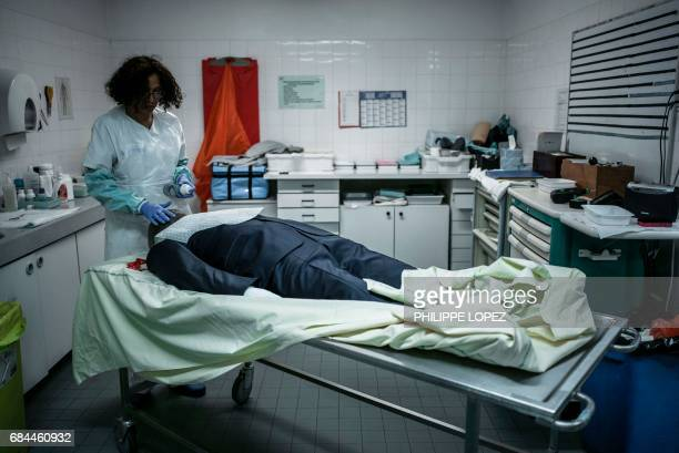 Graphic content / An employee prepares a corpse at the morgue of the Hospital Bichat Claude Bernard in Paris on May 11 2017 / AFP PHOTO / PHILIPPE...