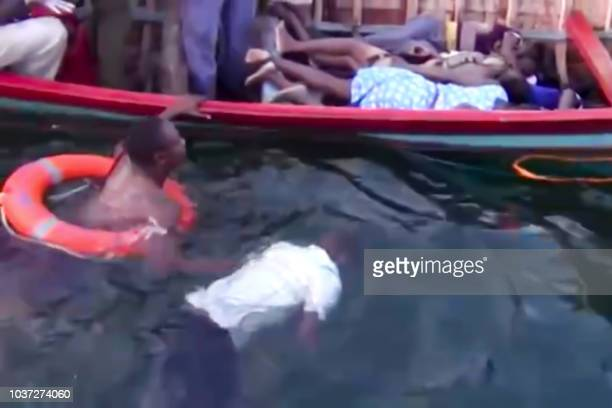 Graphic content / An image grab taken from a video provided by Tanzanias StarTV channel reportedly shows people removing bodies of victims from the...