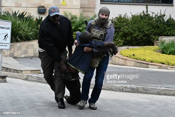 Graphic content / An injured man is evacuated from the scene of an explosion at a hotel complex in Nairobi's Westlands suburb on January 15 in Kenya...