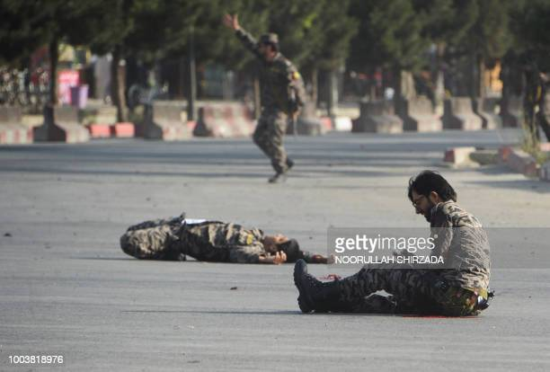 Graphic content / An injured member of the Afghan security forces sits on the ground next to the dead body of a colleague following a suicide attack...