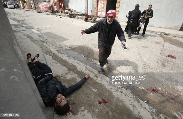 Graphic content / An Iraqi civilian runs towards a man who was injured by a mortar shell fired by Islamic State group jihadists on civilians who were...
