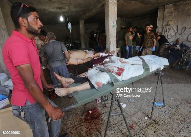 Graphic content / An Iraqi man stands over a body following a suicide attack as people were escaping the Old City of Mosul on June 23 2017 at a...