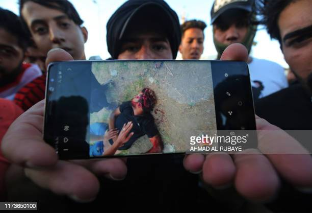 Graphic content / An Iraqi protester displays a picture on his phone of a fellow protester allegedly shot today during a demonstration against state...