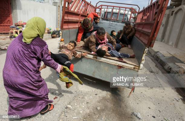 Graphic content / An Iraqi woman pulls a child who was injured by a mortar shell fired by Islamic State group jihadists on a civilian gathering off...