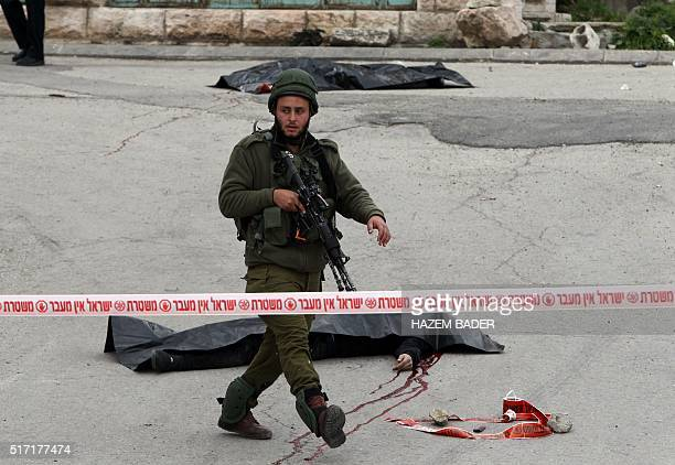 Graphic content / An Israeli solider guards the bodies of two Palestinians who were killed after wounding an Israeli soldier in a knife attack before...