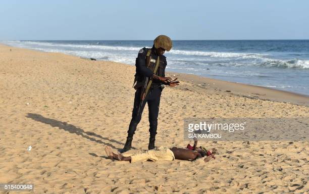 Graphic content / An Ivorian policeman takes a picture of a body on the beach after heavily armed gunmen opened fire on March 13 2016 at a hotel in...