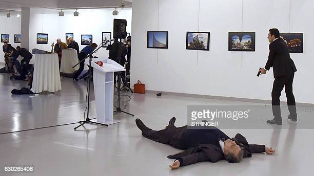 Graphic content / Andrei Karlov the Russian ambassador to Ankara lies on the floor next to his killer Mevlut Mert Altintas who still point his gun to...