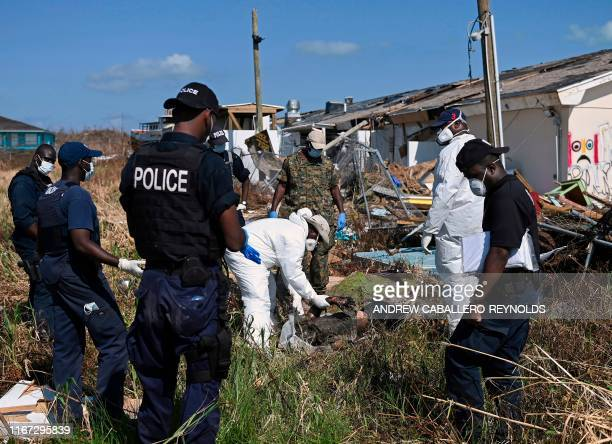 Graphic content / Bahamian police and members of a recovery team lift a body into a body bag in Marsh Harbour Bahamas on September 10 one week after...