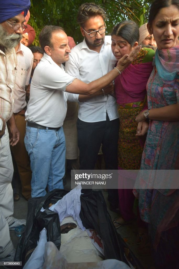 Graphic content / Baljit Kaur and her son Amritbir Singh look at the body of her husband Indian Central Reserve Police Force personnel Raghbir Singh..