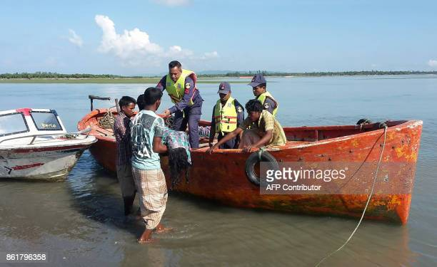 Graphic content / Bangladesh coastguard hand over recovered bodies to local Bangladeshi locals after recovering it from the Naf river estuary near...