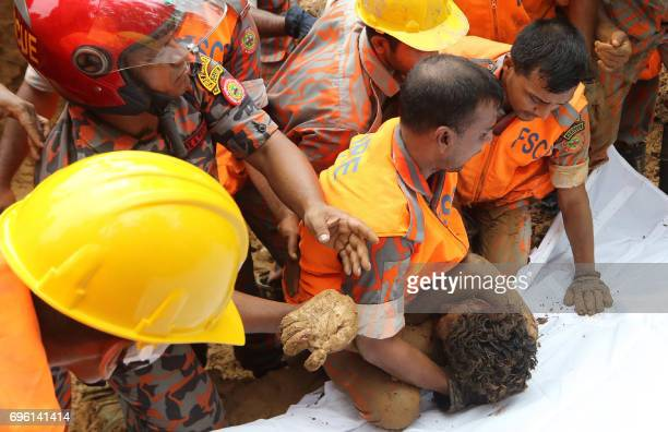 Graphic content / Bangladeshi firefighters recover a dead body at the site of a landslide in Rangamati on June 15 2017 Emergency workers in...