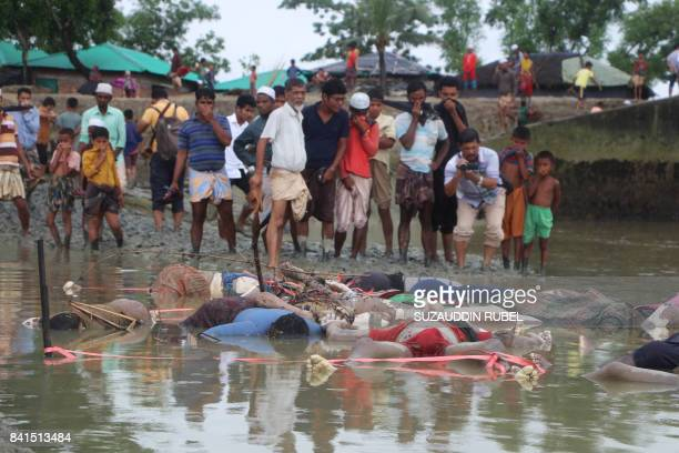 Graphic content / Bangladeshi onlookers stand next to bodies washed up on the banks of the Naf river in Teknaf on September 1 2017 The United Nations...