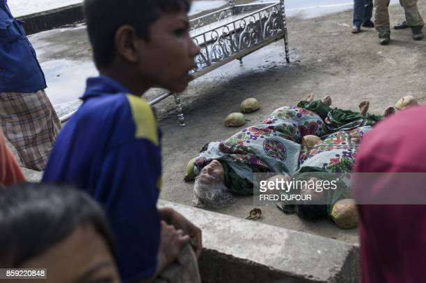 Graphic content / Bangladeshi people gather around the bodies of Rohingya Muslim refugees on Shah Porir Dwip Island near Teknaf on October 9 after a...