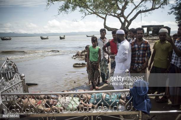 Graphic content / Bangladeshi people look at the bodies of Rohingya Muslim refugees on the beach of Shah Porir Dwip Island on October 9 after a boat...