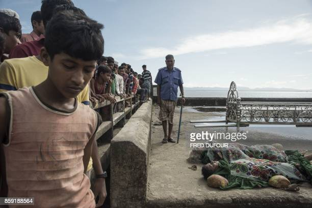 Graphic content / Bangladeshi people look at the bodies of Rohingya Muslim refugees at the pier of Shah Porir Dwip Island on October 9 after a boat...