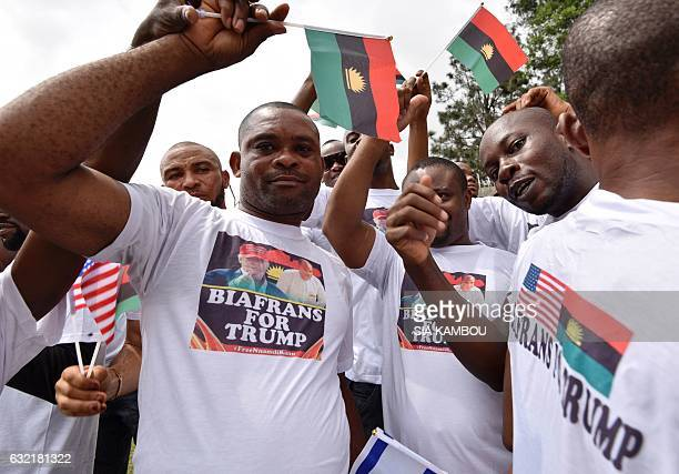 Graphic content / Biafrans wave the flag of the former Republic of Biafra as they rally outside the American Embassy in Abidjan on January 20 as...